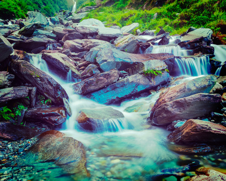 himachal pradesh: Vintage retro effect filtered hipster style travel image of cascade of Bhagsu waterfall in Himalayas. Bhagsu, Himachal Pradesh, India. Polarizer filter used Stock Photo