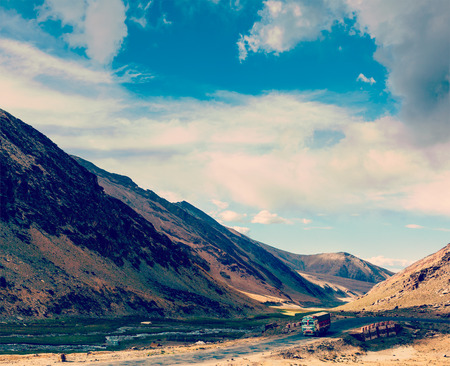 unsurfaced road: Vintage retro effect filtered hipster style travel image of Indian lorry on Manali-Leh Road. Ladakh, India Stock Photo