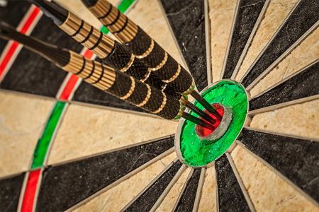 dart: Three darts in bulls eye close up Stock Photo