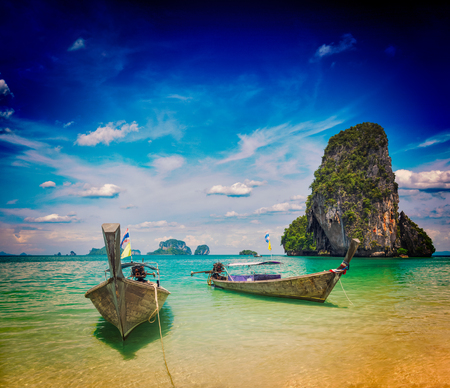 Vintage retro effect filtered hipster style travel image of long tail boats on tropical Pranang beach, Krabi, Thailand photo