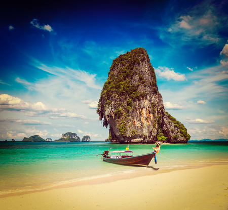 Vintage retro effect filtered hipster style travel image of long tail boat on tropical beach with limestone rock, Krabi, Thailand photo