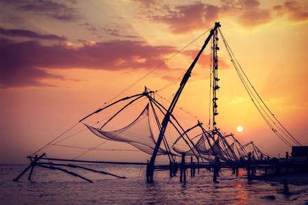 medias de red: Fishnets chinos en puesta del sol. Kochi, Kerala, India Foto de archivo