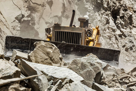 Bulldozer doing road construction in Himalayas Stock Photo
