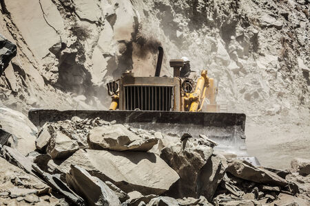 unsurfaced road: Bulldozer doing road construction in Himalayas Stock Photo