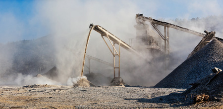 polluted: Industrial background - crusher rock stone crushing machine at open pit mining and processing plant for crushed stone, sand and gravel Stock Photo
