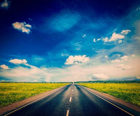 dia soleado: Imagen filtrada efecto estilo inconformista retro vintage del concepto de fondo de viaje - carretera en la pradera de florecimiento de primavera