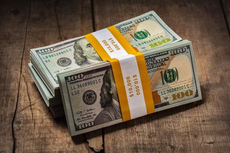 cash money: Financiación de las empresas creativas ganar dinero concepto - pilas de nuevos $ 100 edición 2013 banknotes paquetes sobre fondo de madera