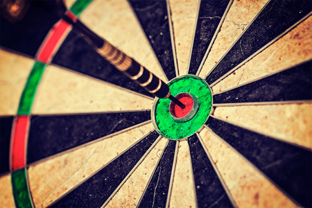 Vintage retro effect filtered hipster style image of   -Success hitting target aim goal achievement concept background - dart in bulls eye close up Фото со стока