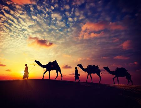 animales del desierto: Imagen filtrada efecto estilo inconformista retro vintage de Rajasthan Viajes - dos camelleros indios camelleros con camellos siluetas en las dunas del desierto de Thar en la puesta del sol. Jaisalmer, Rajasthan, India Foto de archivo