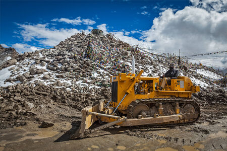 KHARDUNG LA PASS, INDIA - SEPTEMBER 12, 2012: Road construction at Kardung La - the highest motorable highest vehicle-accessible pass pass (5602 m) in the world. The pass is strategically important to India as it is used to carry supplies to the Siachen G Editorial