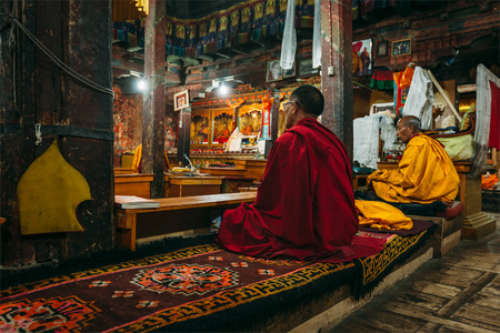 gelugpa: THIKSEY, INDIA - SEPTEMBER 4, 2011: Tibetan Buddhist monks during prayer in Thiksey gompa (Buddhist monastery)  of the Yellow Hat (Gelugpa) sect - the largest gompa in central Ladakh