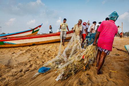 india fisherman: CHENNAI, INDIA - FEBRUARY 10, 2013: Indian fishermen dragging fishing net with their catch from sea on Marina Beach, Chennai, Tamil Nadu