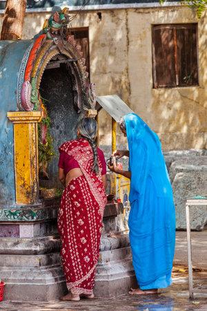 south asian: MADURAI, INDIA - FEBRUARY 16, 2013: Unidentified Indian women worship Hindu god Ganesh in famous Meenakshi Amman Temple - historic Hindu temple located in temple city Madurai
