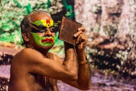 kathakali: KOCHI, INDIA - FEBRUARY 24, 2013: Unidentified Kathakali exponent preparing for performance by applying face make-up. Kathakali is the classical dance form of Kerala