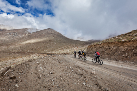 unsurfaced road: KARDUNG LA PASS, INDIA - SEPTEMBER 5, 2011: Bicycle tourists in Himalayas asceinding to Khardung La the highest  motorable pass in the world. Himalayan bycicle tourism is gaining popularity all over the world