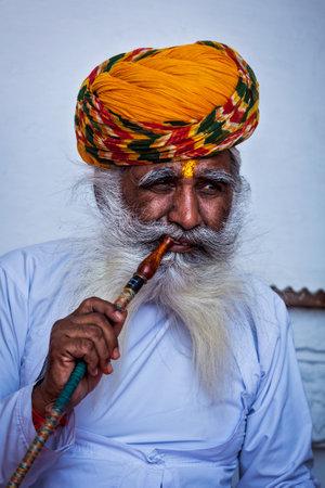 waterpipe: Jodhpur, India - 26 de noviembre de 2012: Hombre indio viejo fuma narguile (pipa de agua) en la fortaleza de Mehrangarh. El concepto de la pipa de agua se cree que se origin� en la India Editorial