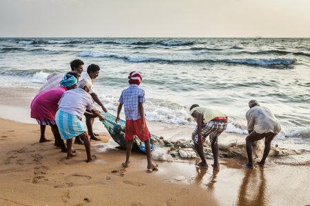 tamil nadu: CHENNAI, INDIA - FEBRUARY 10, 2013: Indian fishermen dragging fishing net with their catch from sea on Marina Beach, Chennai, Tamil Nadu