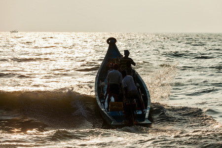 india fisherman: CHENNAI, INDIA - FEBRUARY 10, 2013: Group of Indian fishermen going into the sea on boat for fishing on sunrise