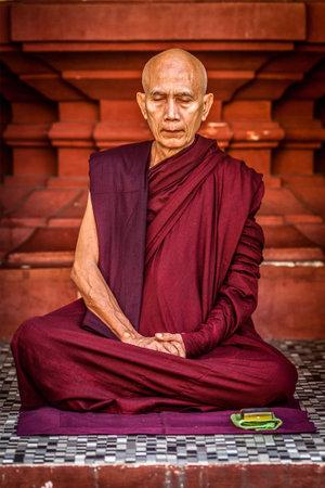 ascetic: YANGON, MYANMAR - JANUARY 3, 2014: Ascetic Buddhist monk meditating in Shwedagon Paya pagoda