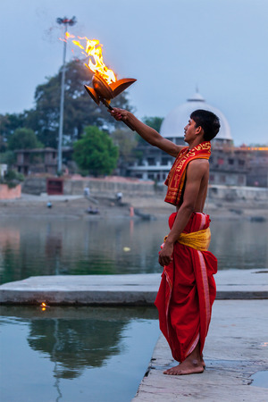 pooja: UJJAIN, INDIA - APRIL 23, 2011: Brahmin performing Aarti pooja ceremony on bank of holy river Kshipra. Aarti is Hindu religious ritual of worship, part of puja when light is offered to one or more deities