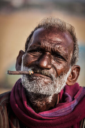 CHENNAI, INDIA - FEBRUARY 10, 2014: Unidentified old fisherman smoking on Marina beach in Chennai, Tamil Nadu, India