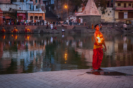 madhya pradesh: UJJAIN, INDIA - APRIL 23, 2011: Brahmin performing Aarti pooja ceremony on bank of holy river Kshipra. Aarti is Hindu religious ritual of worship, part of puja when light is offered to one or more deities