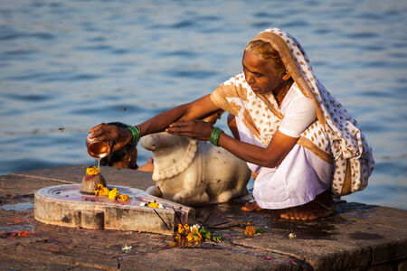 pooja: MAHESHWAR, INDIA - APRIL 26: Indian woman performs morning pooja on sacred river Narmada ghats on April 26, 2011 in Maheshwar, Madhya Pradesh, India. To Hindus Narmada is one of 5 holy rivers of India