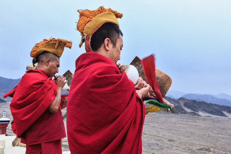 ladakh: THIKSEY, INDIA - SEPTEMBER 4, 2011: Two Tibetan Buddhist monks blowing conches during morning pooja, Thiksey gompa, Ladakh, India Editorial
