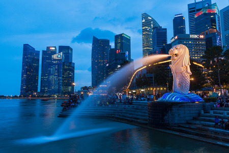 merlion: SINGAPORE - JANUARY 1, 2014: Night view of Singapore Merlion at Marina Bay against Singapore skyline. Merlion is a well-known tourist icon, mascot and national personification of Singapore
