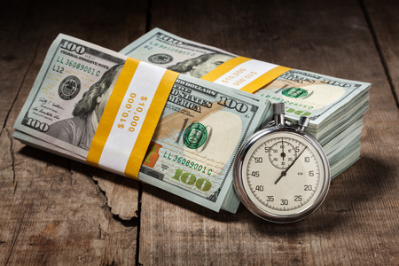 Time is money loan concept background - stopwatch and stack of new 100 US dollars 2013 edition banknotes bills bundles on wooden background photo