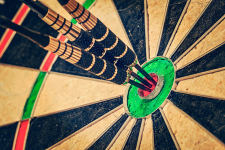 achievement concept: Vintage retro effect filtered hipster style image of  - Success hitting target aim goal achievement concept background - three darts in bull Stock Photo