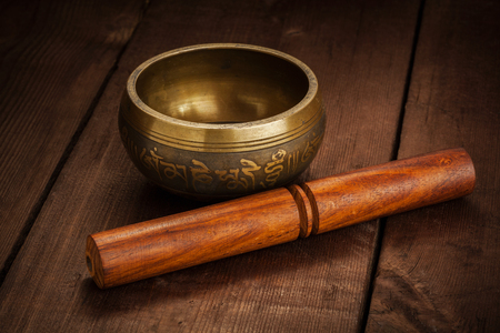 rin gong: Tibetan buddhist singing bowl, rin gong, Himalayan bowl or suzu gong for  meditation, music, relaxation, and personal well-being with mallet on wooden background Stock Photo
