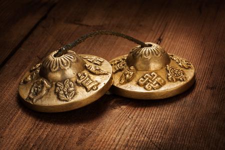 cymbals: Tibetan Buddhist tingsha cymbals on wooden background