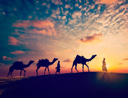 Vintage retro effect filtered hipster style image of Rajasthan travel background - two indian cameleers camel drivers with camels silhouettes in dunes of Thar desert on sunset. Jaisalmer, Rajasthan, India Archivio Fotografico