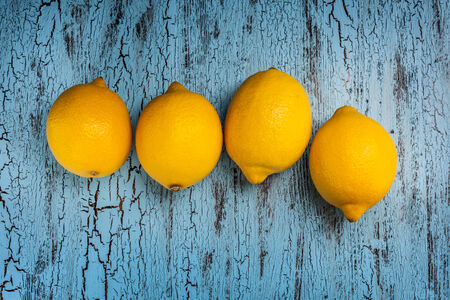 Four fresh ripe yellow lemons on blue wooden background photo