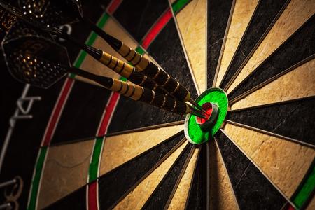 Three darts in bull\'s eye close up