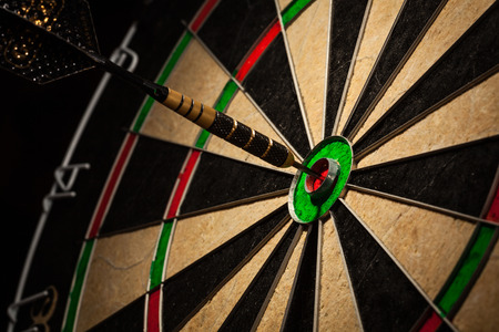 goals: Dart in bulls eye close up Stock Photo