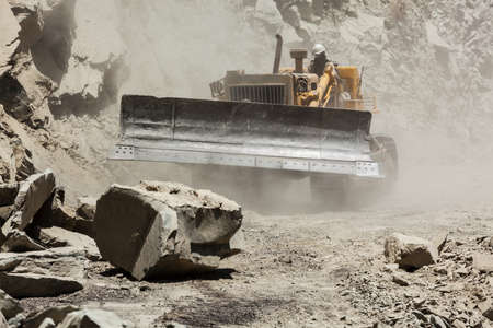 unsurfaced road: Bulldozer cleaning landslide on road in Himalayas