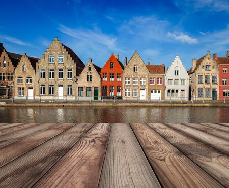 row of houses: Wooden planks table with European town in background