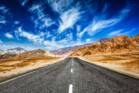 plains indian: Road in Himalayas with mountains Stock Photo