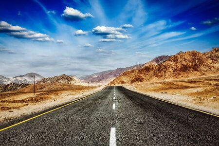 plains indian: Travel forward concept background wallpaper - road in Himalayas and blue sky dramatic clouds. Ladakh, Jammu and Kashmir, India