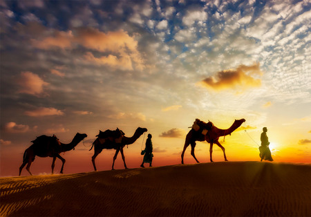 Reise-Hintergrund - zwei Kameltreiber (Kameltreiber) mit Kamelen Silhouetten in den Dünen der Wüste auf Sonnenuntergang