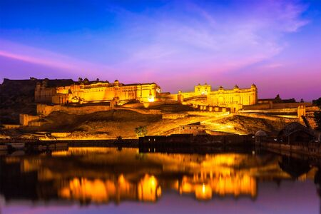 amber: Indian landmark - Amer Fort (Amber Fort) illuminated at night - one of principal attractions in Jaipur, Rajastan, India refelcting in Maota lake in twilight Stock Photo
