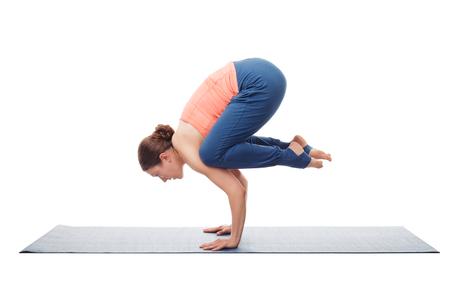 yogini: Beautiful sporty fit yogini woman practices yoga asana Bakasana - crane pose arm balance isolated on white