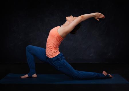 Beautiful sporty fit yogini woman practices yoga asana  Anjaneyasana - low crescent lunge pose in surya namaskar on dark background