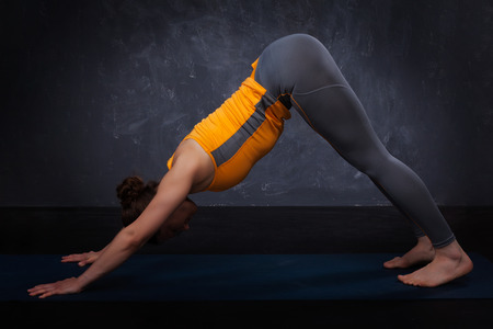 dog pose: Beautiful sporty fit yogini woman practices yoga asana adhomukha svanasana - downward facing dog pose on dark  background
