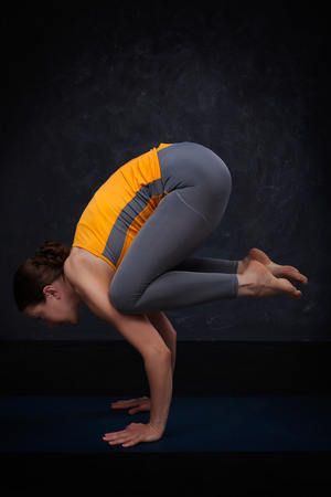 asana: Beautiful sporty fit yogini woman practices yoga asana Bakasana - crane pose arm balance  on dark background