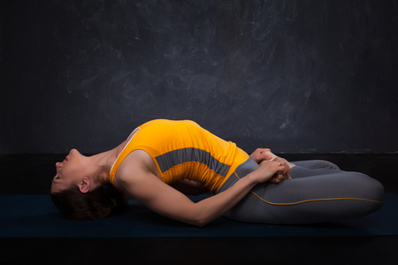 yogini: Beautiful sporty fit yogini woman practices yoga asana Matsyasana - fish pose on dark background