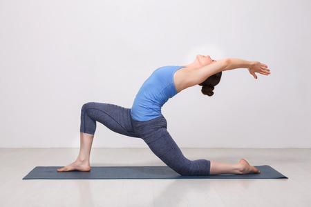 Beautiful sporty fit yogini woman practices yoga asana  Anjaneyasana - low crescent lunge pose in surya namaskar in studio Archivio Fotografico