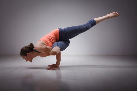 фитнес: Красивая спортивный подходят йогини практики йоги женщина асана эка пада koundinyasana 1 - 1 позе, посвященный мудрец Koundinya создают в студии